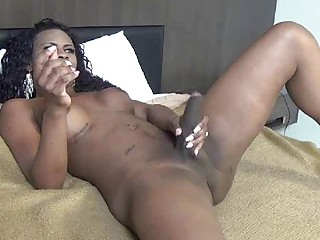 Hung black tranny hottie strokes her monster cock in bed
